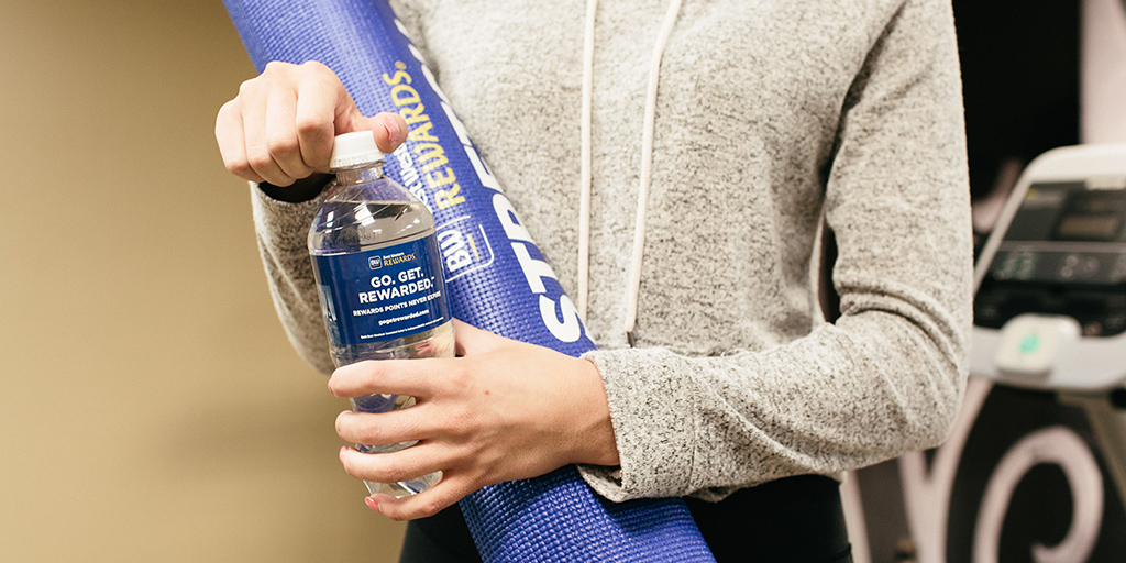 Woman holding BW rewards yoga mat opening a BW Rewards branded water bottle
